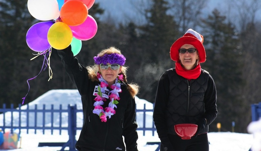 Two lady spectators with funny hats and baloons.