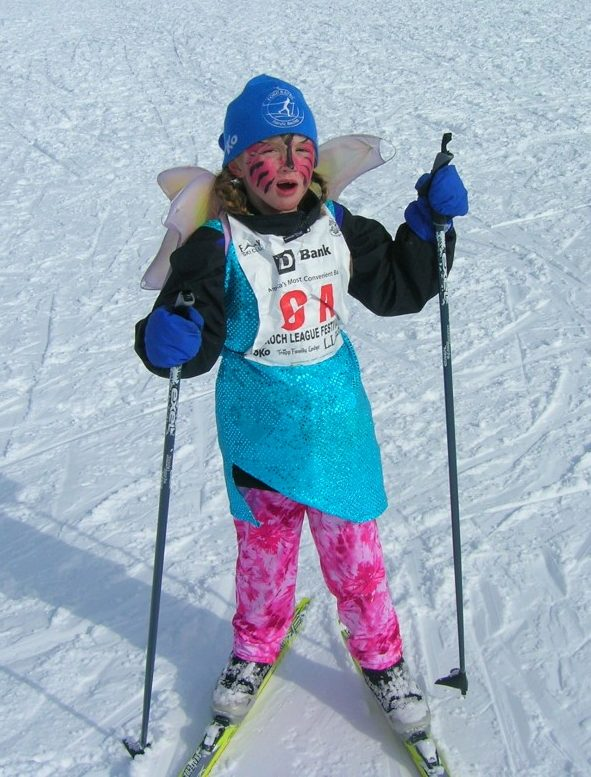 Young Nordic skier with fairy wings and face paint.